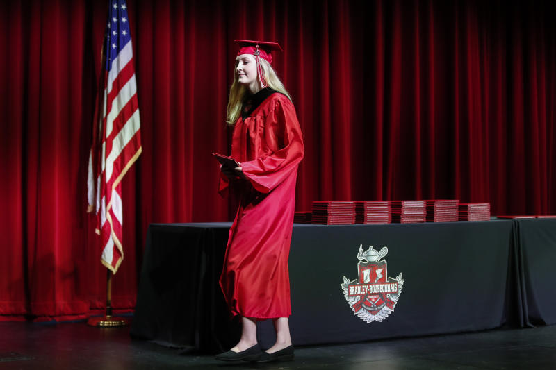 A student picks up her diploma during a graduation ceremony at Bradley-Bourbonnais Community High School on May 6, 2020 in Bradley, Illinois. (Photo: KAMIL KRZACZYNSKI/AFP via Getty Images)