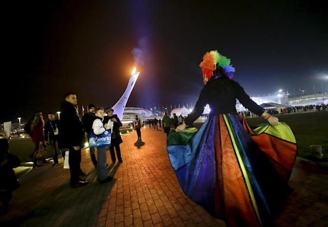 Vladimir Luxuria, right, a former Communist lawmaker in the Italian parliament and prominent crusader for transgender rights, walks through the Olympic Plaza as visitors look on at left at the 2014 Winter Olympics, Monday, Feb. 17, 2014, in Sochi, Russia. Luxuria was soon after detained by police upon entering the Shayba Arena to attend a women's ice hockey match. (AP Photo/David Goldman)