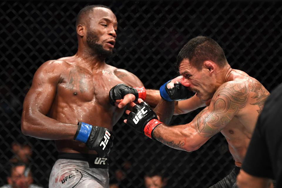 SAN ANTONIO, TEXAS - JULY 20:  (L-R) Leon Edwards of Jamaica punches Rafael Dos Anjos of Brazil in their welterweight bout during the UFC Fight Night event at AT&T Center on July 20, 2019 in San Antonio, Texas. (Photo by Josh Hedges/Zuffa LLC/Zuffa LLC via Getty Images)