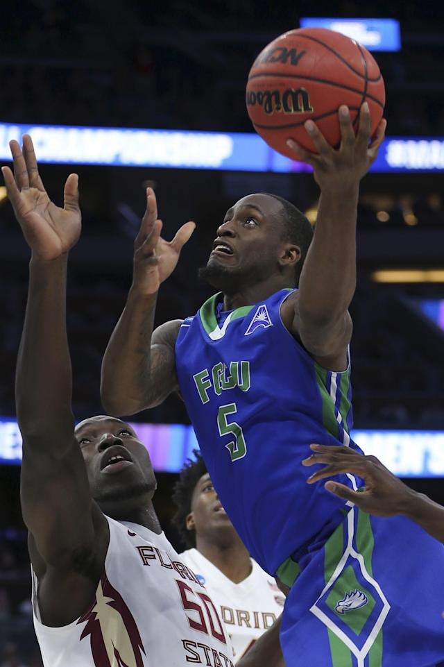 Florida Gulf Coast guard Zach Johnson (5) goes up for a shot against Florida State center Michael Ojo (50) during the second half of the first round of the NCAA college basketball tournament, Thursday, March 16, 2017 in Orlando, Fla. (AP Photo/Gary McCullough)