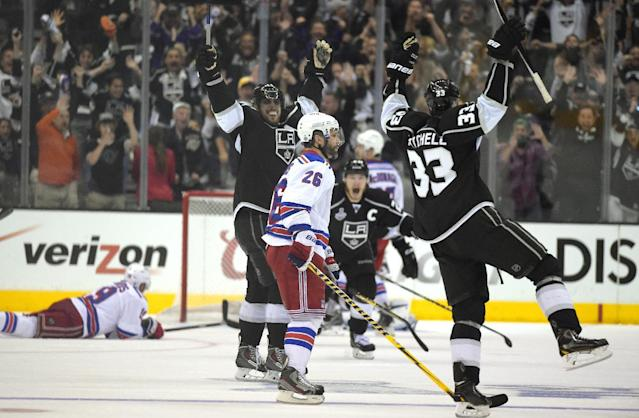 Los Angeles Kings right wing Dustin Brown, center, celebrates after scoring the game-winning goal along with center Anze Kopitar, second from left, of Slovenia, and defenseman Willie Mitchell, right, as New York Rangers center Brad Richards, left, lies on the ice and Martin St. Louis (26) watches during the second overtime period in Game 2 of the NHL hockey Stanley Cup Finals, Saturday, June 7, 2014, in Los Angeles. The Kings won 5-4. (AP Photo/Mark J. Terrill)