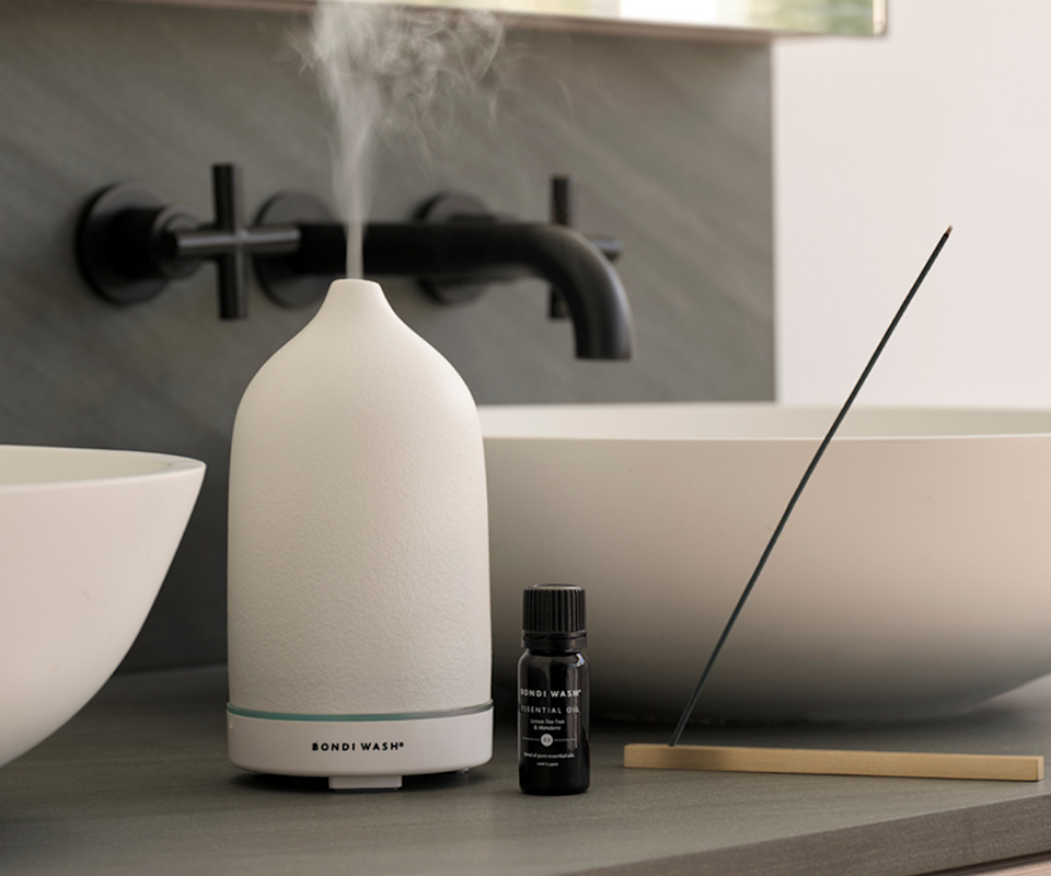 An image of the white Bondi Wash aromatherapy diffuser next to a sink in a bathroom.
