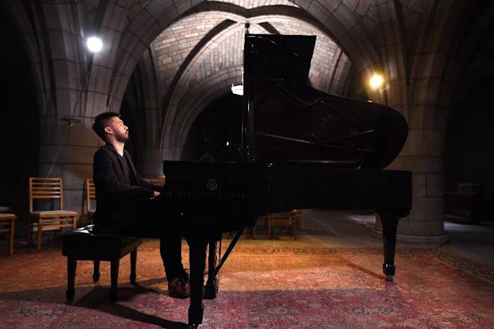 Musician Conrad Tao, a young classical composer warms-up before his concert in the basement crypt in Harlem's Church of the Intercession November 5, 2015 in New York (AFP Photo/Timothy A. Clary)