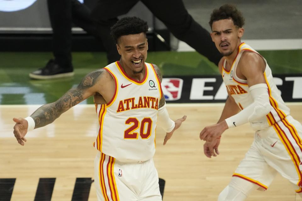 Atlanta Hawks' John Collins reacts after a dunk assisted by Trae Young during the second half of Game 1 of the NBA Eastern Conference basketball finals game against the Milwaukee Bucks Wednesday, June 23, 2021, in Milwaukee. (AP Photo/Morry Gash)