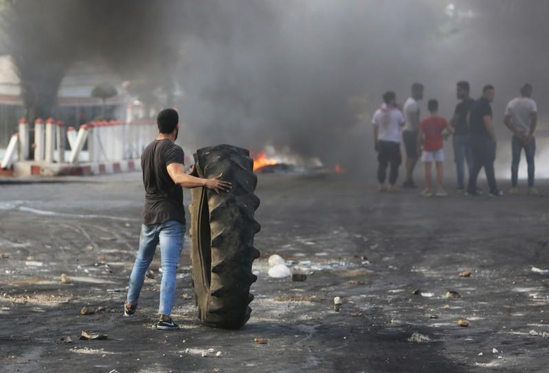 A demonstrator holds a tire during a protest targeting the government over an economic crisis, in Nabatiyeh
