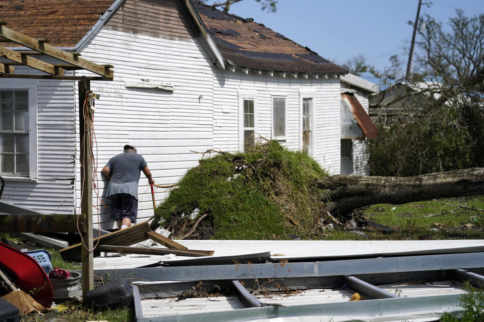 Bradley Beard walks alongside his heavily damaged home, that was moved off its foundation piers, as he searches for his water shutoff valve, in Hackberry, La., in the aftermath of Hurricane Laura, Saturday, Aug. 29, 2020. (AP Photo/Gerald Herbert)