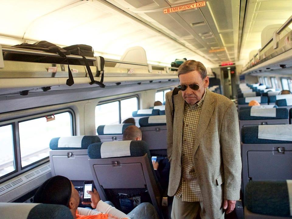a man walking down the aisle of a crowded amtrak car