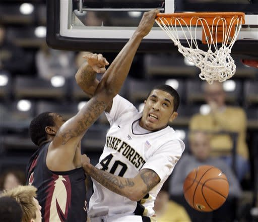 Florida State's Xavier Gibson, left, dunks over Wake Forest's Ty Walker, right, during the first half of an NCAA college basketball game in Winston-Salem, N.C., Wednesday, Jan. 25, 2012. (AP Photo/Chuck Burton)