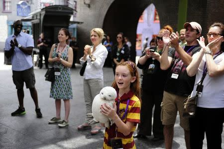Fianna Roberts-Squier, 8, applauds during a media preview for The Wizarding World of Harry Potter-Diagon Alley at the Universal Orlando Resort in Orlando, Florida June 19, 2014. REUTERS/David Manning
