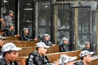 Egyptian security peronnel line the public gallery as Muslim Brotherhood members appear in the caged dock at a trial hearing in July 2018
