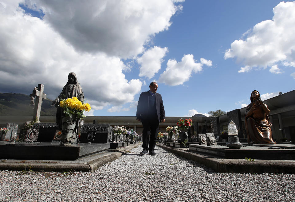 """FILE - In this Sunday, Sept. 27, 2020 file photo, Rev. Mario Carminati walks in a cemetery in Casnigo, near Bergamo, Italy. After the European Union passed the death toll of half a million citizens lost to the coronavirus on Wednesday, Feb. 10, 2021, the EU Commission chief said that stalling rollout of the vaccines could be partly blamed on the bloc being over-optimistic, over-confident and plainly """"too late."""" (AP Photo/Antonio Calanni, File)"""