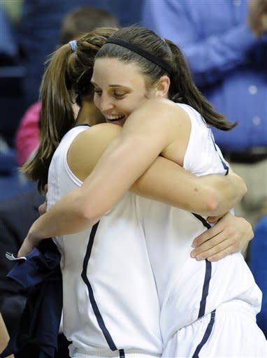 Connecticut's Kelly Faris hugs teammate Caroline Doty after scoring her 1000th career point during the second half of Connecticut's 90-30 victory over Seton Hall in an NCAA college basketball game in Storrs, Conn., Saturday, Feb. 23, 2013. Faris scored a game-high 18 points in the win. (AP Photo/Fred Beckham)