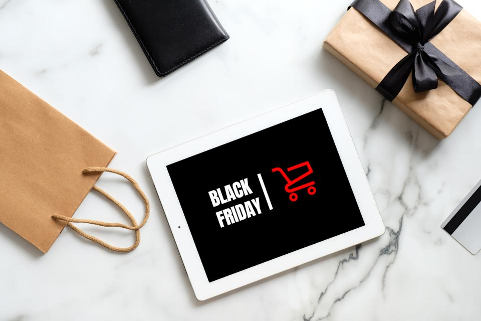 """Black friday sale concept. Tablet pad with sign """"Black friday"""", gift box, shopping bag on marble table. Flat lay, top view, overhead"""