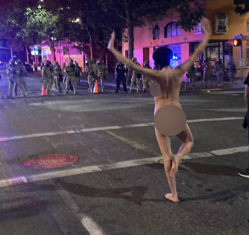 Photo shows 'Naked Athena' posing standing on one leg with her arms up.
