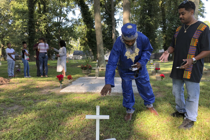 Andre Bradshaw, left, and Eric Jackson stand at an unmarked grave at the Tucker Family Cemetery in Hampton, Va. on Friday, Aug. 23, 2019. They are part of a larger family that traces its roots back to the first enslaved Africans to arrive in what is now Virginia in 1619. (AP Photo/Ben Finley)