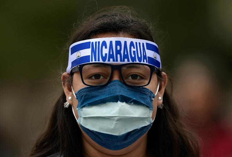 A woman wearing a mask bearing the colors of the Nicaraguan flag attends a demonstration to protest against the political situation in Nicaragua at the Colon square in Madrid (AFP Photo/OSCAR DEL POZO)