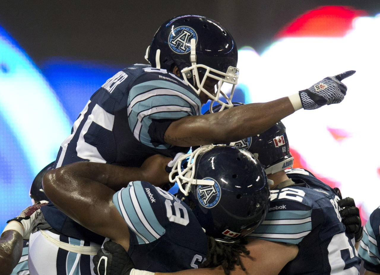 Toronto Argonauts wide receiver Sammie Parker (85) is hoisted aloft by teammates Stephen Good (62) and Darion Smith (69) after scoring the game winning touchdown in fourth quarter CFL pre-season action against the Montreal Alouettes in Toronto on Tuesday June 19, 2012. THE CANADIAN PRESS/FRANK GUNN