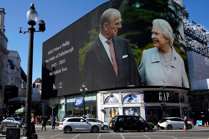 Images of the queen and the duke are displayed on screens at Piccadilly Circus in London while the funeral is held at Windsor.
