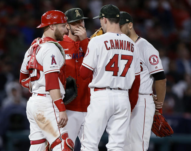Los Angeles Angels pitching coach Doug White, second from left, and catcher Jonathan Lucroy, left, talk to starting pitcher Griffin Canning during the fifth inning of the team's baseball game against the Kansas City Royals in Anaheim, Calif., Saturday, May 18, 2019. (AP Photo/Alex Gallardo)