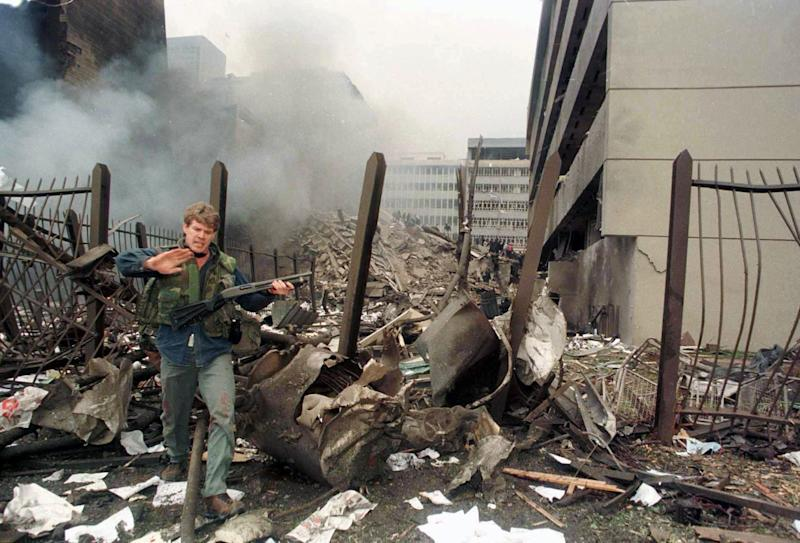A U.S. embassy official secures the area around the embassy building after a powerful bomb blast in Nairobi