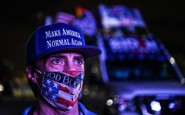 A nervous-looking Democrat supporter at a watch party in Miami - GETTY IMAGES