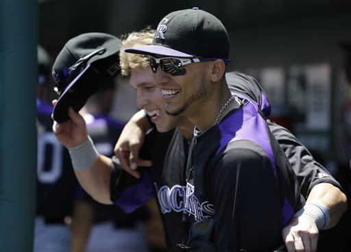 Colorado Rockies left fielder Carlos Gonzalez, right, and teammate right fielder Corey Dickerson, left, head out to the field during the first inning of a baseball game against the Washington Nationals at Nationals Park, Saturday, June 22, 2013, in Washington. (AP Photo/Carolyn Kaster)