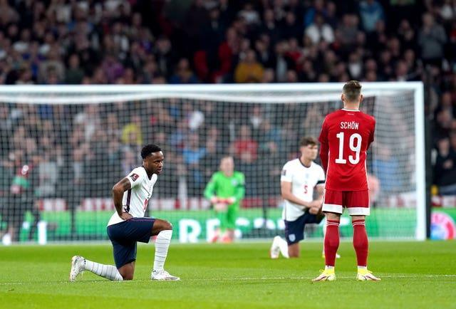 England's Raheem Sterling takes a knee as Hungary's Szabolcs Schon remains standing