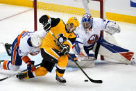Pittsburgh Penguins' Sidney Crosby, center, cannot get his stick on the puck in front of New York Islanders goaltender Ilya Sorokinin, right, with Islanders' Ryan Pulock (6) defending during the first period of Game 1 of an NHL hockey Stanley Cup first-round playoff series in Pittsburgh, Sunday, May 16, 2021. (AP Photo/Gene J. Puskar)