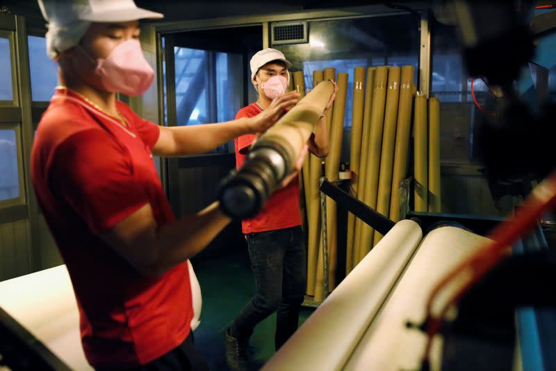 Staff work inside a non woven filter fabric factory, where the fabric is used to make surgical face masks, in Taoyuan,