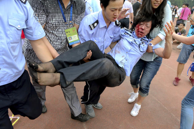 A security officer and others attempt to carry a policewoman injured in a stampede by fans of David Beckham at a university in Shanghai on Thursday, June 20, 2013. Fans eager to see the soccer superstar stormed a police cordon Thursday in a stampede at a Shanghai university that injured seven people including five security personnel. (AP Photo) CHINA OUT