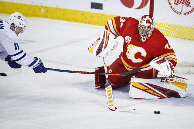 Toronto Maple Leafs' Zach Hyman, stretches to reach the puck in front off Calgary Flames goalie David Rittich during the first period of an NHL hockey game, Thursday, Dec. 12, 2019 in Calgary, Alberta. (Jeff McIntosh/The Canadian Press via AP)