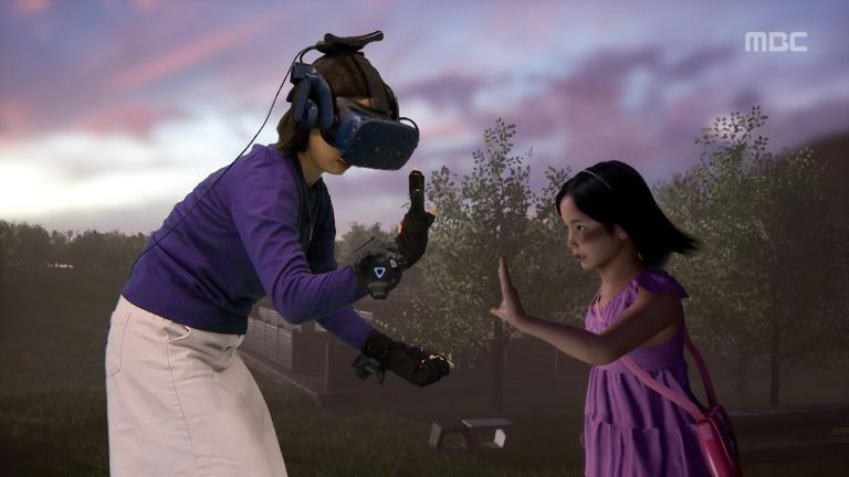 Jang Ji-sung (L) 'met' her dead daughter Na-yeon via virtual reality for a South Korean TV show (AFP Photo/Handout)