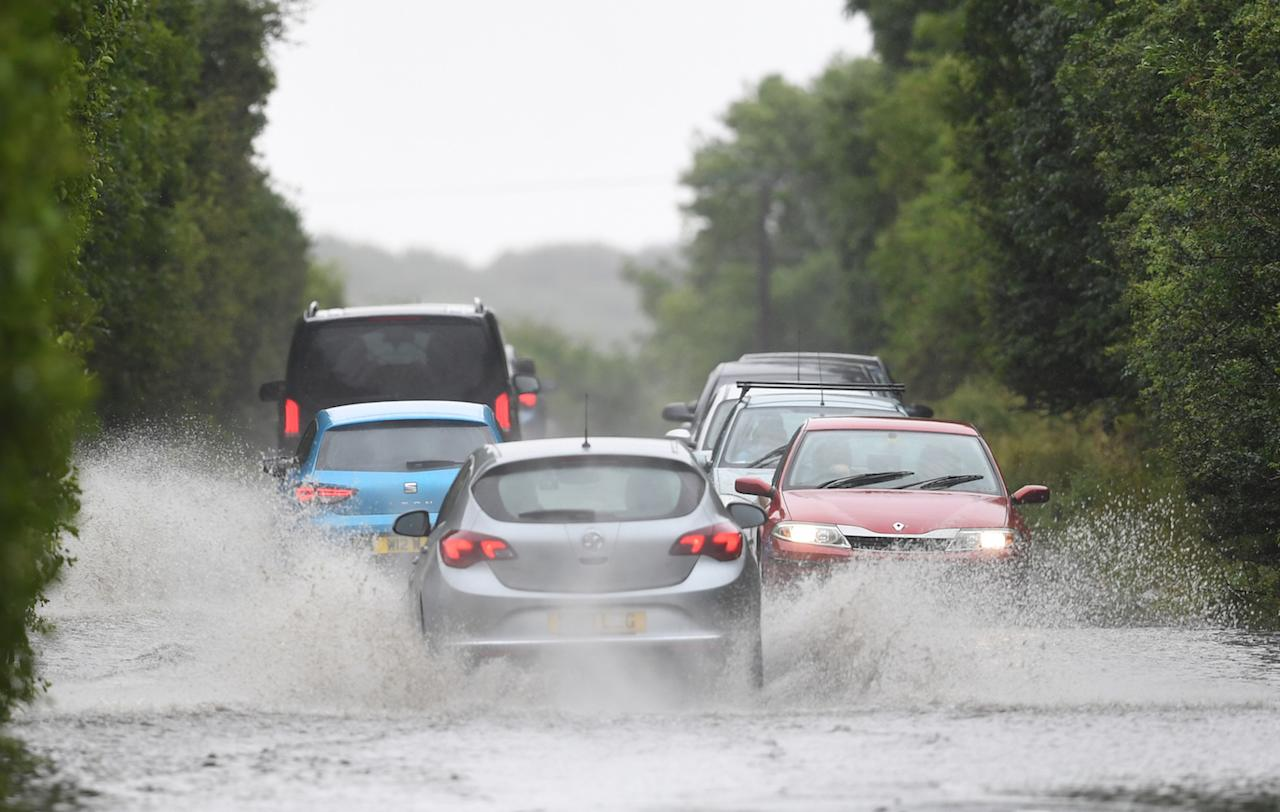 Cars make their way through standing water on the A47 near Peterborough (Picture: PA)
