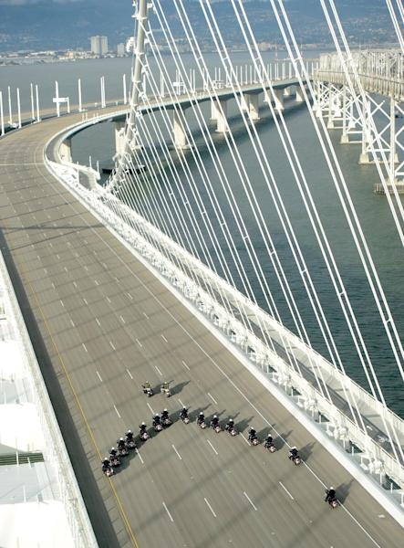 In this photo taken on Monday, Sept. 2, 2013, provided by the Bay Area Toll Authority, a phalanx of police officers cross the San Francisco-Oakland Bay Bridge after leading a procession marking the east span's opening, in San Francisco. At the modest inaugural ceremony, the new, self-anchored suspension bridge with its looming, single white tower was praised as a dramatic safety upgrade over its predecessor. It also was held up as a beautiful example of public art. (AP Photo/Bay Area Toll Authority, Noah Berger) MAGS OUT, NO SALES