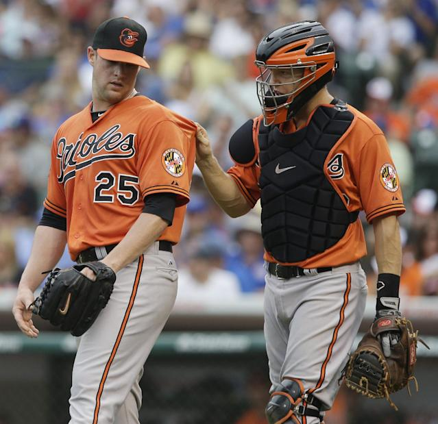 Baltimore Orioles catcher Nick Hundley, right, talks to starter Bud Norris during the second inning of an interleague baseball game against the Chicago Cubs in Chicago, Saturday, Aug. 23, 2014. (AP Photo/Nam Y. Huh)