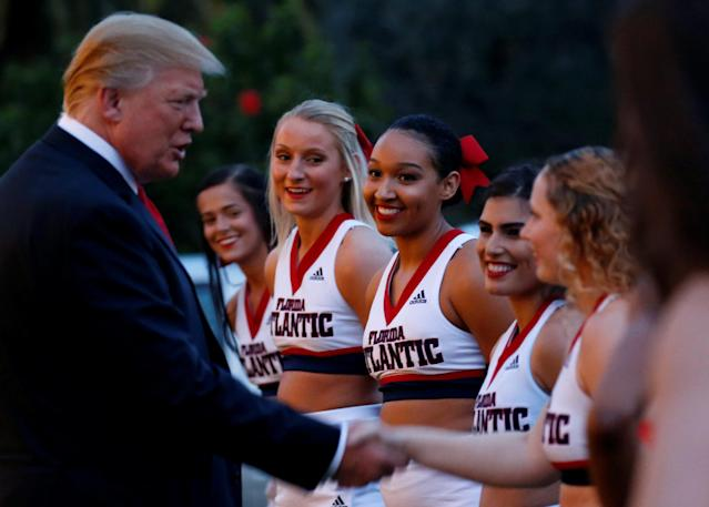 U.S. President Donald Trump greets cheerleaders with the Florida Atlantic University Marching Band before hosting a Super Bowl LII watch party at Trump International Golf Club in Palm Beach, Florida, U.S., February 4, 2018. REUTERS/Leah Millis