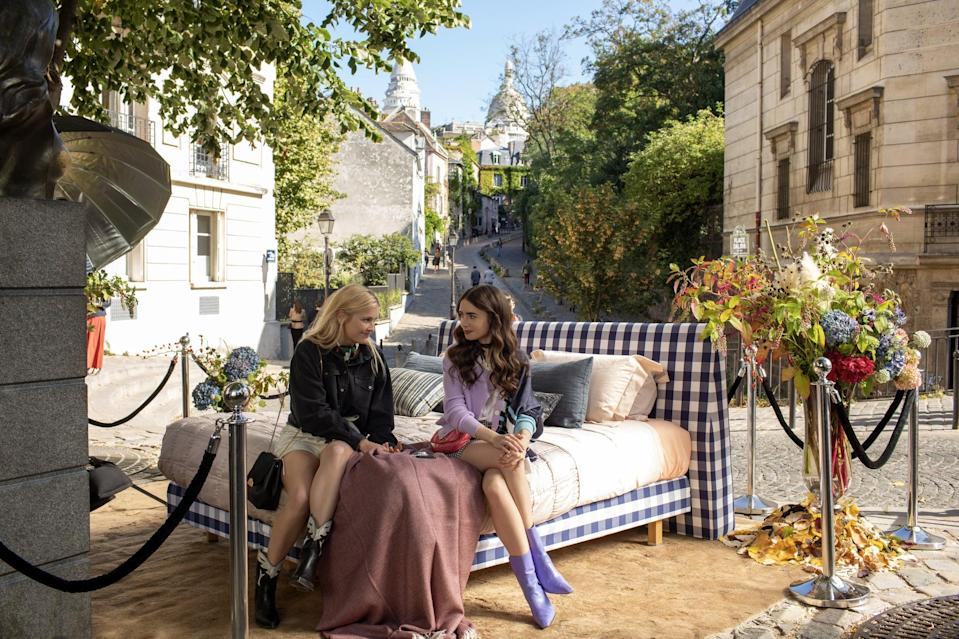 EMILY IN PARIS (L to R) CAMILLE RAZAT as CAMILLE and LILY COLLINS as EMILY in episode 105 of EMILY IN PARIS Cr. CAROLE BETHUEL/NETFLIX  2020