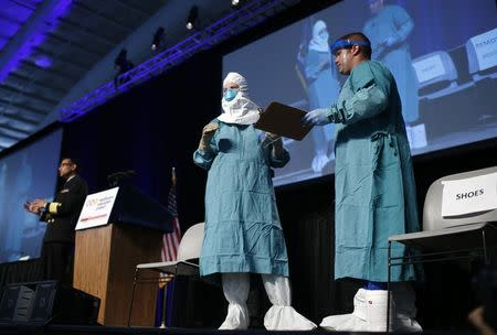 Barbara Smith, a registered nurse with Mount Sinai Medical Health Systems, St. Luke's and Roosevelt Hospitals in New York, and Bryan Christensen (R) of the of the CDC's Domestic Infection Control Team for Ebola demonstrate putting on personal protective equipment (PPE) during an Ebola educational session for healthcare workers at the Jacob Javits Convention center in New York, October 21, 2014.  REUTERS/Mike Segar