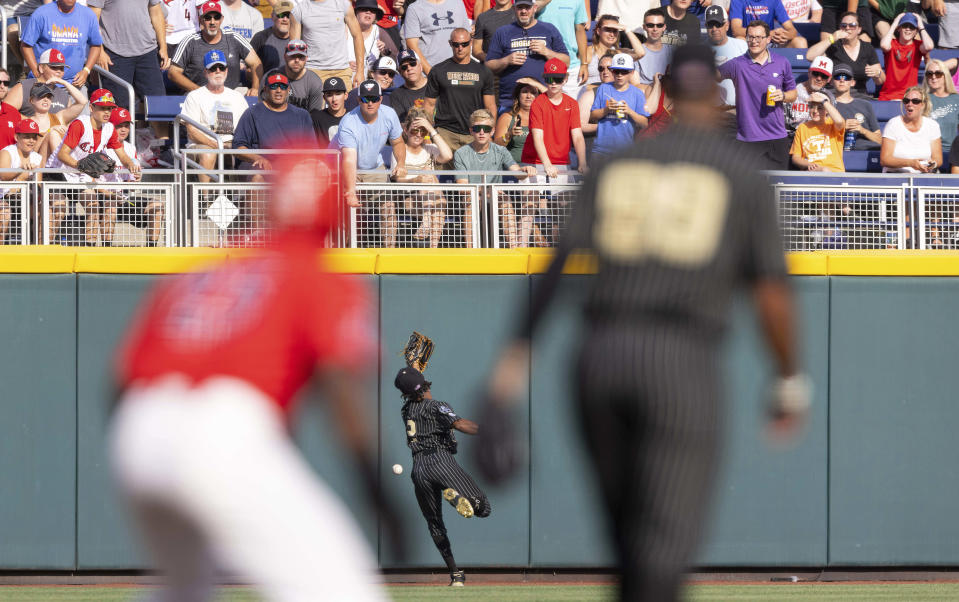 Vanderbilt's Javier Vaz (2) cannot reach a fly ball hit by Arizona's Branden Boissiere to left field to bat in two runners in the first inning during a baseball game in the College World Series, Saturday, June 19, 2021, at TD Ameritrade Park in Omaha, Neb. (AP Photo/Rebecca S. Gratz)