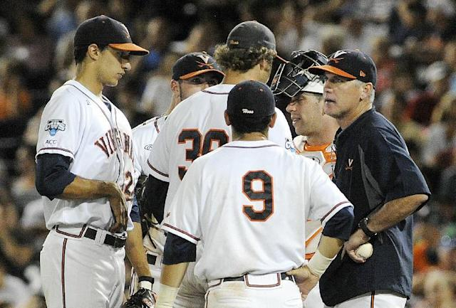 Virginia coach Brian O'Connor, right, talks to Virginia pitcher Austin Young (39) in the sixth inning of the opening game of the best-of-three NCAA baseball College World Series finals against Vanderbilt in Omaha, Neb., Monday, June 23, 2014. (AP Photo/Eric Francis)