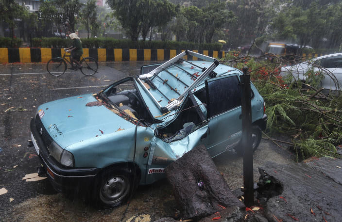 A car stands damaged after a tree fell on it in Mumbai, India, Monday, May 17, 2021. Cyclone Tauktae, roaring in the Arabian Sea was moving toward India's western coast on Monday as authorities tried to evacuate hundreds of thousands of people and suspended COVID-19 vaccinations in one state. (AP Photo/Rafiq Maqbool)