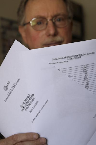 Mark Klein holds up documents while posing for photographs at his home in Alameda, Calif., Tuesday, June 11, 2013. Before there was Edward Snowden and the leaking of an explosive court document showing wide-spread government eavesdropping, there was Mark Klein _ a San Francisco telecommunications technician who alleged that AT&T was allowing government spies to siphon vast amounts of customer data without warrants. Armed with Klein's allegations, lawyers representing consumers upset with what they called an illegal government invasion of their privacy filed a high-profile lawsuit seeking to invalidate the same provisions of the Foreign Intelligence Surveillance Act at the center of the latest public outcry. (AP Photo/Jeff Chiu)