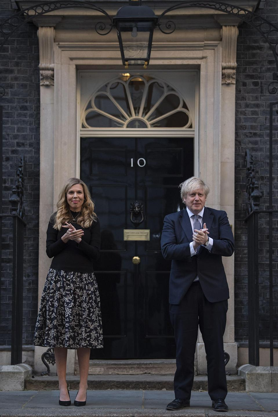 Boris Johnson and Carrie Symonds stand in Downing Street, London, to join in the applause to salute local heroes during the nationwide Clap for Carers to recognise and support NHS workers and carers fighting the coronavirus pandemic (Photo: Victoria Jones/PA Images)