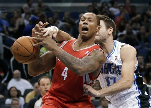 Houston Rockets' Greg Smith (4) loses the ball as he is fouled by Orlando Magic's Josh McRoberts (17) during the first half of an NBA preseason basketball game, Friday, Oct. 26, 2012, in Orlando, Fla. (AP Photo/John Raoux)