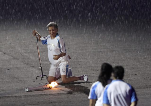 2016 Rio Paralympics - Opening ceremony - Maracana - Rio de Janeiro, Brazil - 07/09/2016. Brazilian Paralympic runner Marcia Malsar falls while carrying the torch as rain falls during the opening ceremony. REUTERS/Ueslei Marcelino FOR EDITORIAL USE ONLY. NOT FOR SALE FOR MARKETING OR ADVERTISING CAMPAIGNS.