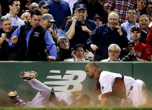Fans react as Boston Red Sox third baseman Will Middlebrooks, left, crashes into catcher David Ross while making the play on a pop foul by Minnesota Twins' Chris Parmelee during the fifth inning of a baseball game at Fenway Park in Boston, Tuesday, May 7, 2013. Middlebrooks made the catch for the out. (AP Photo/Elise Amendola)