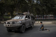 A Taliban fighter prays next a demonstration organized by the Afghan Society of Muslim Youth, demanding the release of frozen international money in Kabul, Afghanistan, Friday, Sept. 24, 2021. (AP Photo/Bernat Armangue)