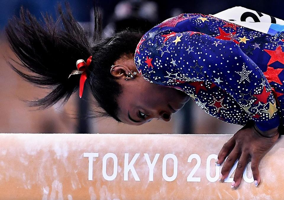 Simone Biles competes on the balance beam in the women's team qualifying Sunday.