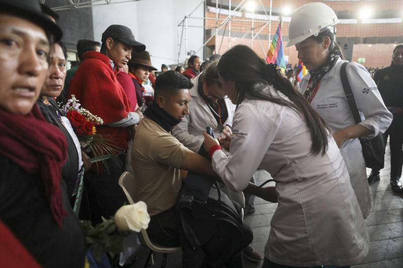 Doctors check the vitals one of several police officers detained by anti-government protesters at the Casa de Cultura in Quito, Ecuador, Thursday, Oct. 10, 2019. An indigenous leader and four other people have died in unrest in Ecuador since last week, the public defender's office said Thursday. (AP Photo/Fernando Vergara)