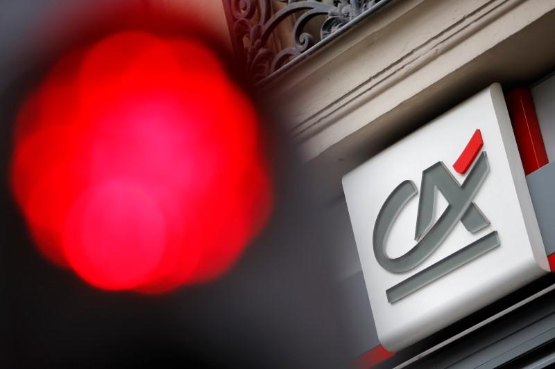 A traffic light shines red near a Credit Agricole logo pictured on a bank branch in Paris